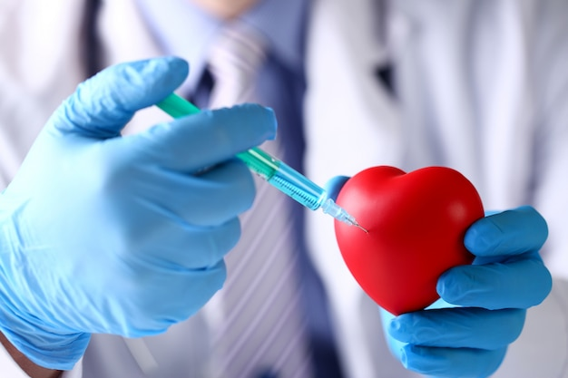Des bras de médecin portant des gants de protection bleus collent une aiguille dans le cœur