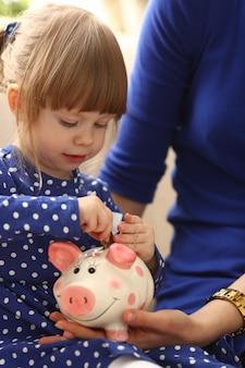 Bras de petite fille enfant mettant des pièces de monnaie dans la tirelire