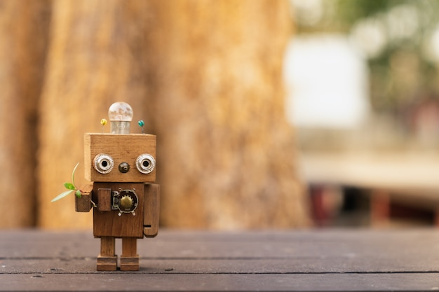 Bras de robot en bois avec des feuilles vertes, concept de technologie écologique.