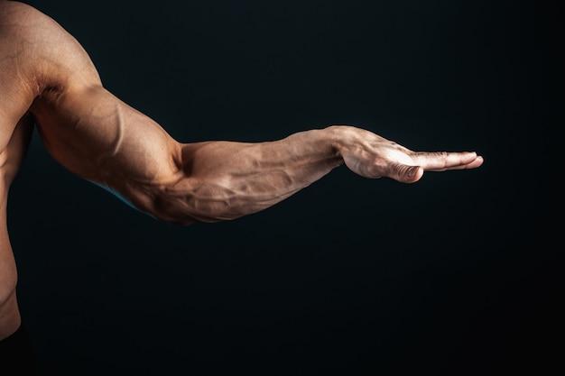 Bras tendu, veines, muscles du culturiste sur un espace sombre, isoler