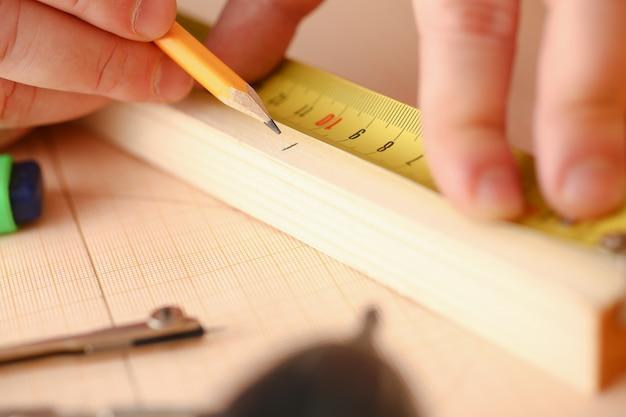 Bras de travailleur mesurant une barre en bois