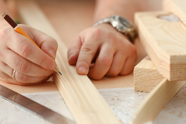 Bras de travailleur mesurant la barre en bois