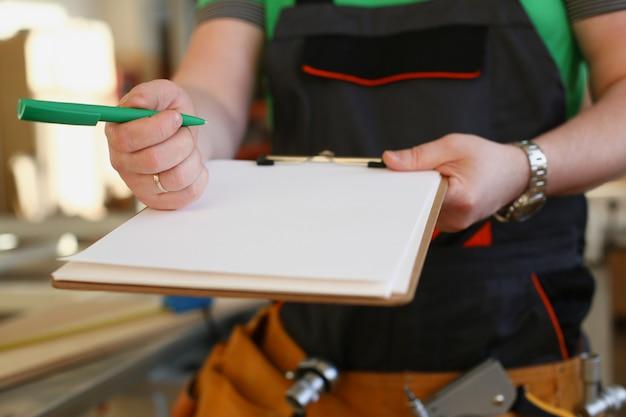 Bras de travailleur offre presse-papiers avec stylo vert