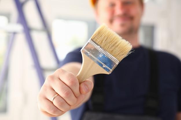 Bras de travailleur souriant tenir pinceau closeup