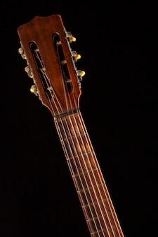 Bras d'une vieille guitare acoustique sur un mur noir.
