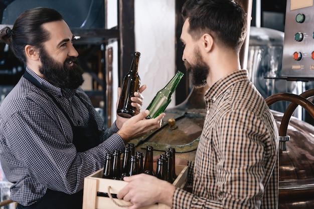 Brasseur choisissant bouteille brune et verte pour ale.
