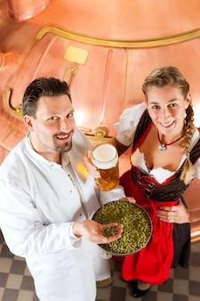 Brasseur et femme avec verre à bière dans une brasserie