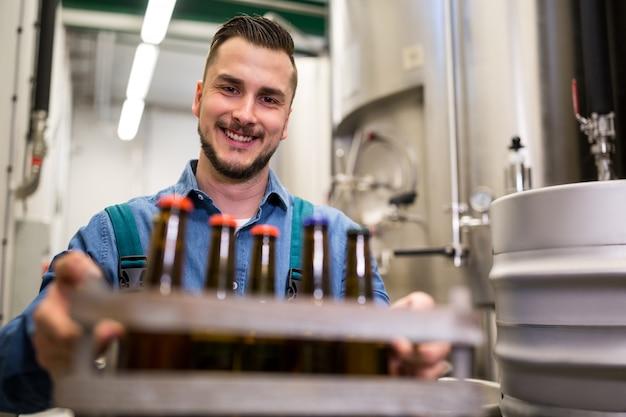 Brasseur tenant des bouteilles de bière dans une caisse