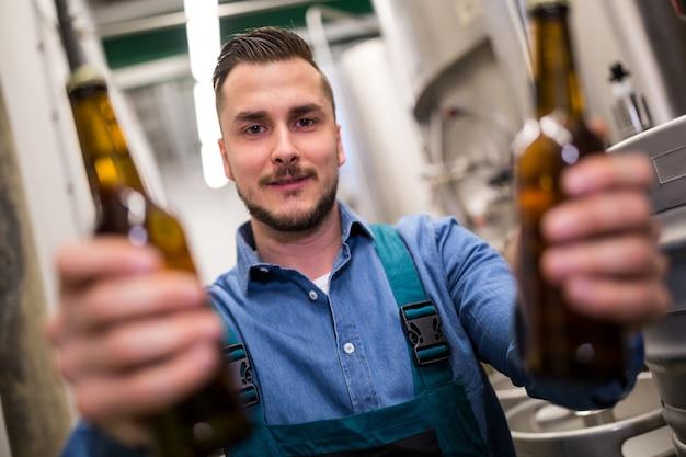 Brasseur tenant deux bouteilles de bière