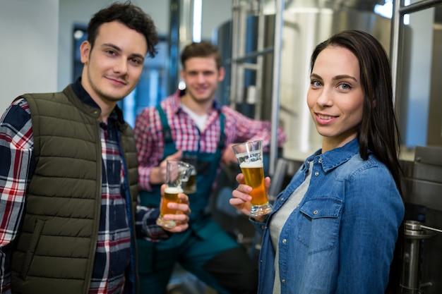Brasseurs tenant des verres à bière à l'usine de brasserie