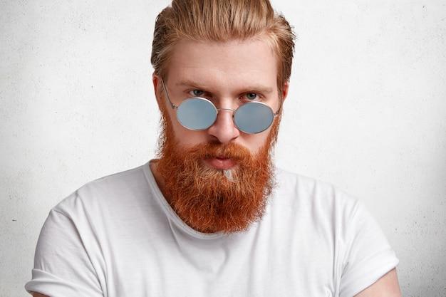 Brave bel homme avec un regard sérieux attrayant, a une barbe et une moustache rousse élégante, porte des lunettes de soleil, habillé avec désinvolture, isolé sur du béton blanc