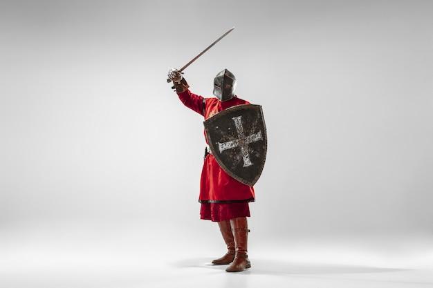Brave chevalier blindé avec combat d'armes professionnelles isolé sur fond de studio blanc. reconstruction historique du combat indigène des guerriers. concept d'histoire, passe-temps, art militaire antique.