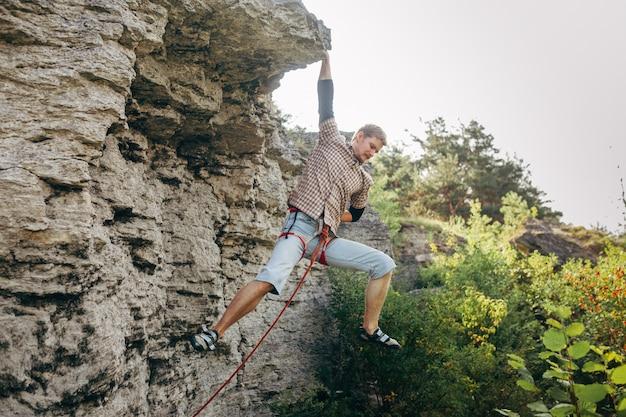Un brave jeune homme gravit la falaise