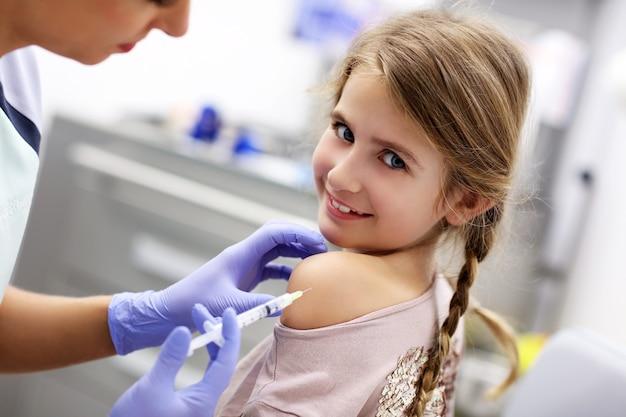 Brave petite fille recevant une injection ou un vaccin avec un sourire
