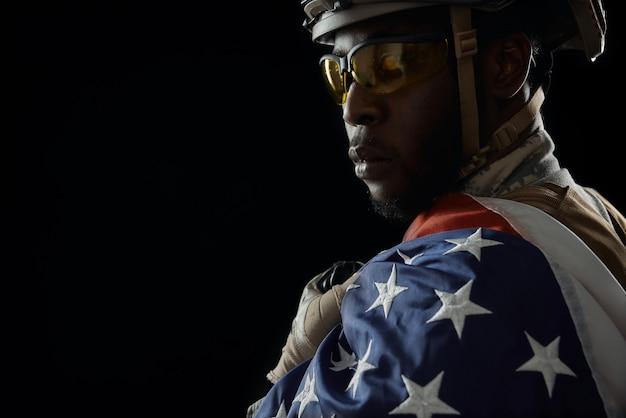 Brave soldat africain posant avec le drapeau national.
