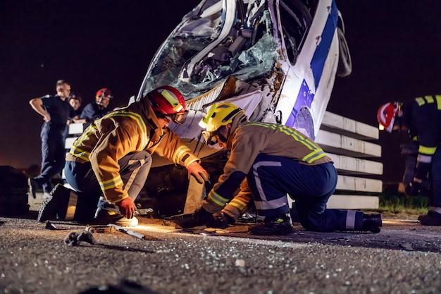 Braves pompiers essayant de libérer l'homme de la voiture accidentée.