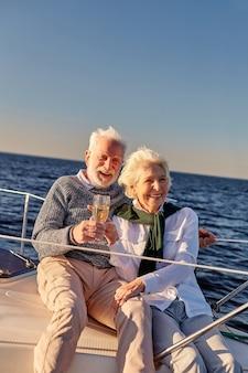 Bravo heureux couple de personnes âgées buvant du vin ou du champagne et souriant tout en célébrant le mariage