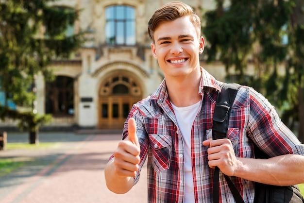 Bravo pour le succès! bel étudiant montrant son pouce vers le haut et souriant tout en se tenant à l'extérieur avec le bâtiment de l'université en arrière-plan