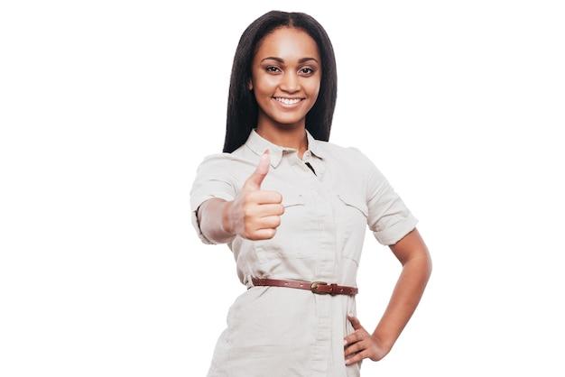 Bravo pour le succès ! souriante jeune femme africaine gardant son pouce levé un sourire en se tenant debout sur fond blanc