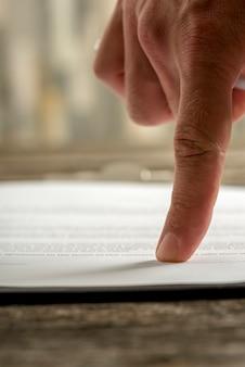 En bref, un seul doigt humain pointant vers la partie signature sur un contrat papier dactylographié.