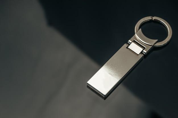 Breloque clé en métal masculin élégant sur verre noir close up