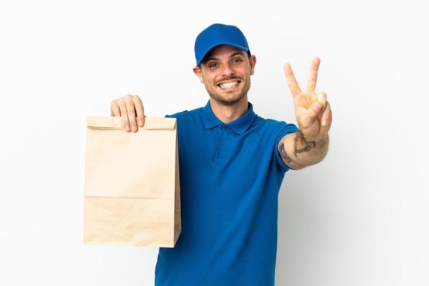 Brésilien prenant un sac de nourriture à emporter isolé sur fond blanc souriant et montrant le signe de la victoire