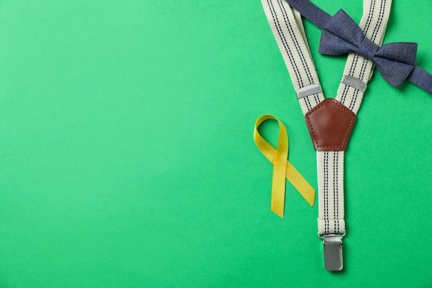 Bretelles, noeud de cravate et ruban de sensibilisation au cancer infantile sur fond vert