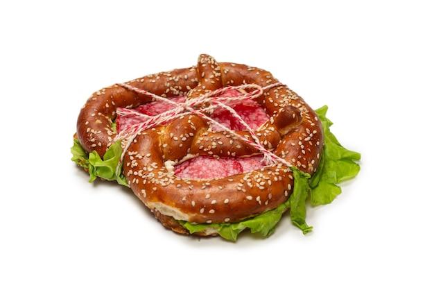 Bretzel au salami et laitue isolé sur fond blanc. collation savoureuse.