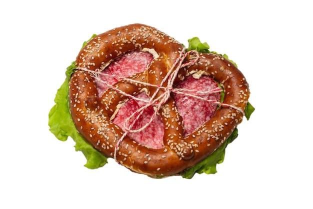 Bretzel au salami et laitue isolé sur une surface blanche. collation savoureuse.