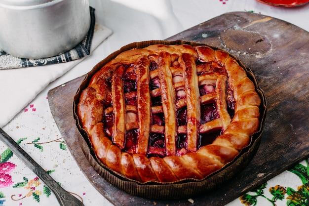 Bretzel formé gâteau fruits avec chocolat rond cuit au four délicieux délicieux brun à l'intérieur de la casserole ronde sur le bureau en bois brun