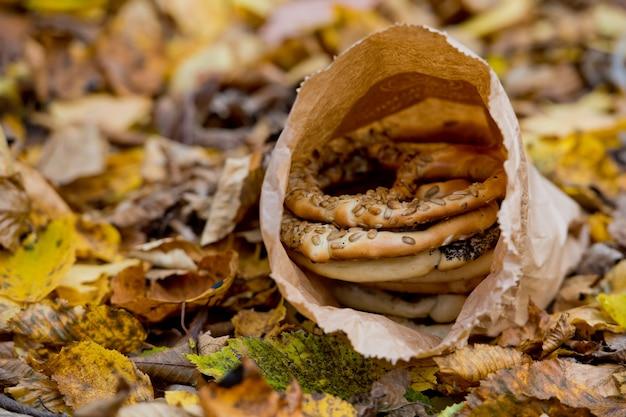 Bretzels assortis frais dans un sac en papier sur fond de feuillage jaune d'automne.