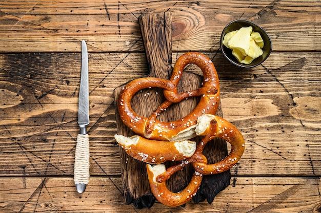 Bretzels cuits au four avec du sel de mer sur une planche à découper en bois rustique