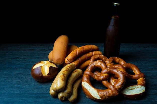 Bretzels et saucisses avec de la bière en bouteille sur une table en bois pour un style de nourriture sombre oktoberfest
