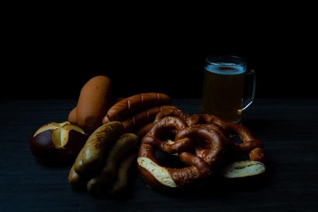 Bretzels et saucisses d'oktoberfest avec pot de bière sur la nourriture foncée de table en bois