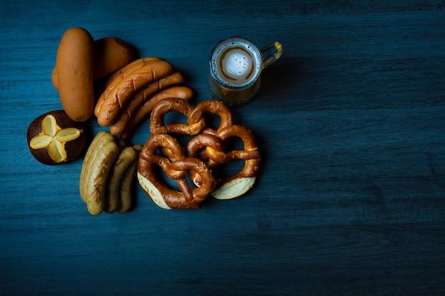 Bretzels et saucisses oktoberfest avec pot de bière sur table en bois de style alimentaire sombre
