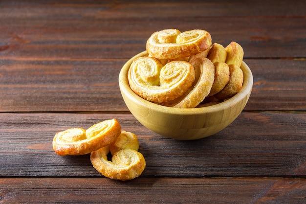 Bretzels sucrés faits de pâte feuilletée dans un bol sur une table en bois