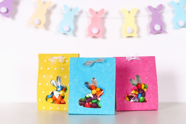 Bricolage de pâques emballant des bonbons de paquet dans un sac avec une silhouette de lapin découpée sur un fond blanc.