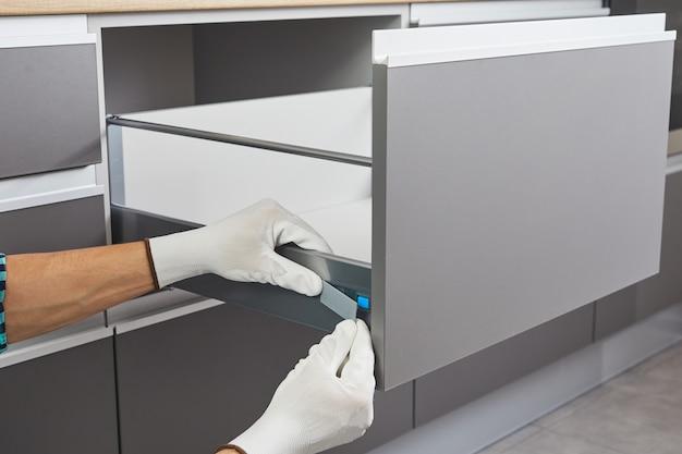 Bricoleur assemblant et installe un tiroir dans la cuisine. le travailleur fixe le mécanisme du meuble du tiroir de l'armoire.