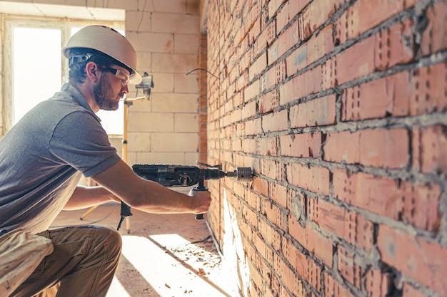 Bricoleur sur un chantier de construction en train de percer un mur avec un perforateur