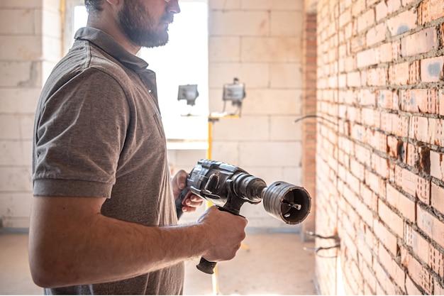 Bricoleur sur un chantier de construction en train de percer un mur avec un perforateur.