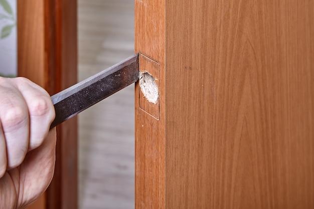 Le bricoleur cisèle le bois le long de la lèvre pour que le verrou de la plaque s'insère.