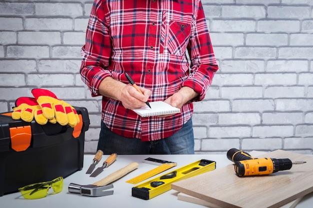 Le bricoleur a fait des croquis dans un cahier. réparateur avec différents outils sur le lieu de travail. notion de bricolage.