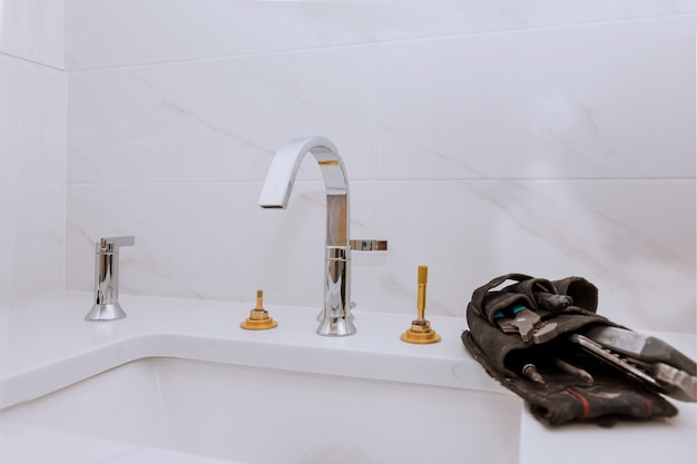 Bricoleur installer un nouveau robinet de lavabo dans la salle de bain