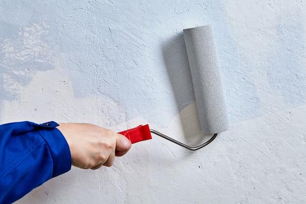 Bricoleur peint les murs à l'intérieur de la maison.