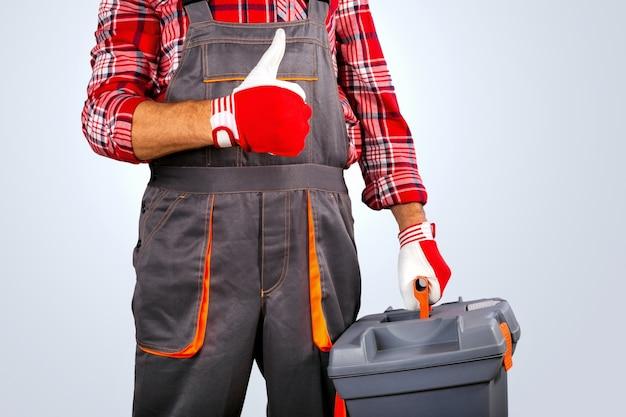 Bricoleur avec le pouce de la boîte à outils sur fond gris.