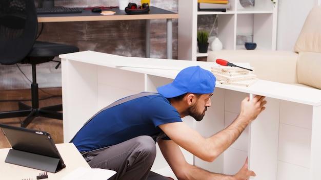 Un bricoleur séduisant assemble de nouveaux meubles pour les propriétaires. travailleur lisant des instructions à partir d'un ordinateur tablette.