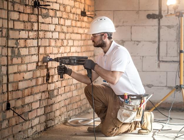 Le bricoleur utilise un marteau-piqueur, pour l'installation, un travailleur professionnel sur le chantier. le concept d'électricien et de bricoleur.