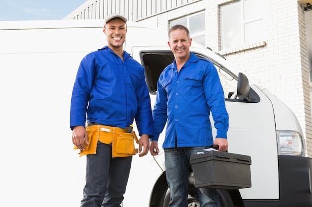 Bricoleurs souriants regardant la caméra devant leur van
