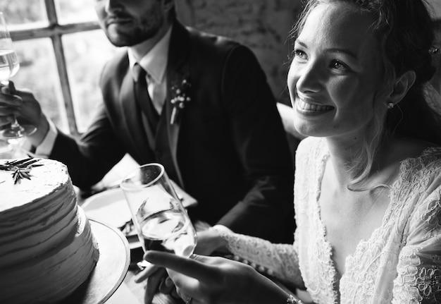 Bride and groom cling wineglasses avec des amis sur la réception de mariage