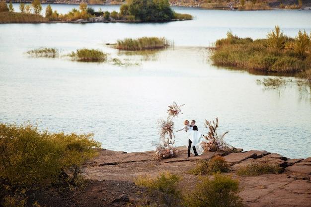 Bride and groom près de la décoration de mariage lors d'une cérémonie sur une falaise de rocher près de l'eau au coucher du soleil